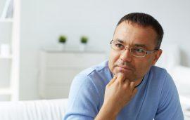 Pensive man in eyeglasses listening to psychologist